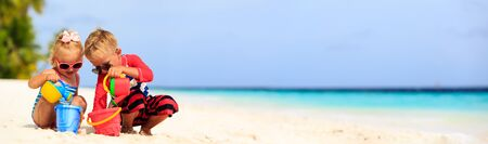 cute little boy and toddler girl play on beach, panorama