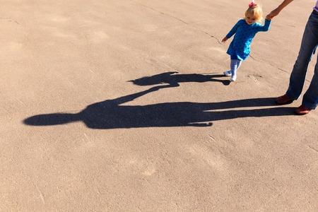 cogidos de la mano: Sombras de la madre y la pequeña hija de la mano en la carretera