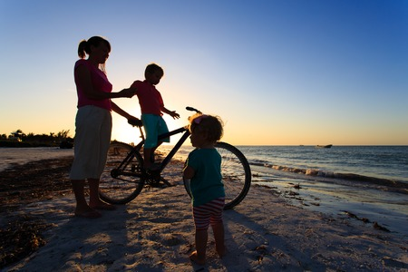 brother: mother with two kids biking at sunset beach