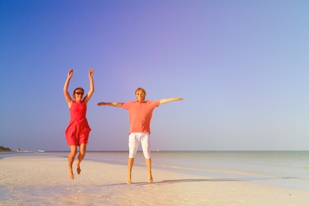 mujer enamorada: Happy couple jumping on the summer tropical beach
