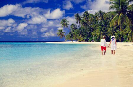 luna de miel: feliz pareja amorosa caminando en la playa del verano tropical