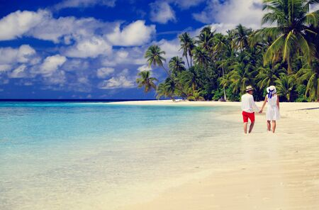 honeymoon couple: happy loving couple walking on summer tropical beach Stock Photo