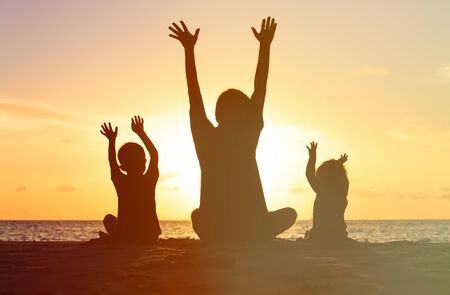 children love: Silhouette of happy father and kids at sunset beach