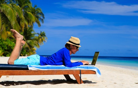 distant work: man with laptop on tropical beach, distant work concept Stock Photo