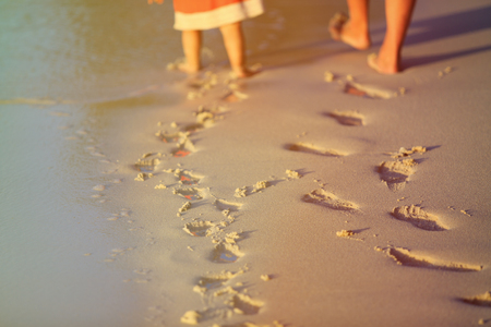 mother and little daughter walking on beach leaving footprint in sand