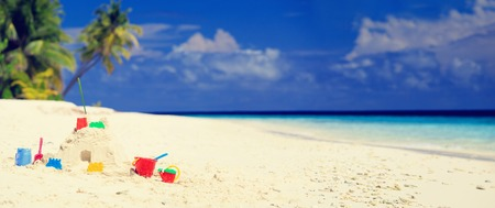 children sandcastle: Sand castle on tropical beach and kids toys, panorama Stock Photo