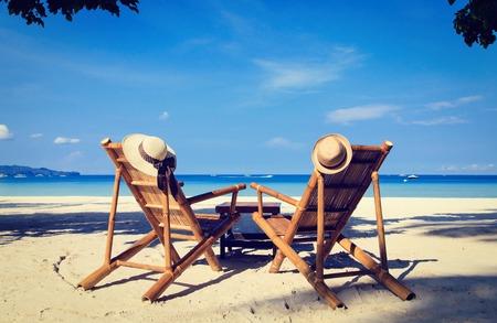 luna de miel: sombreros en sillas de playa de arena de playa tropical en Boracay, Filipinas