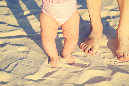 bare woman: mother and baby feet on summer beach