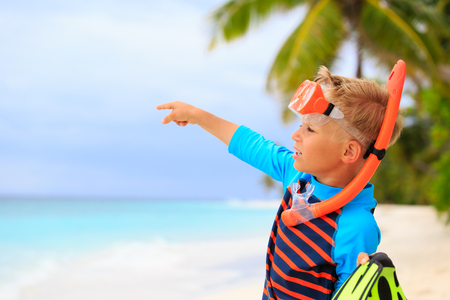 flippers: little boy going on snorkel with flippers at tropical beach