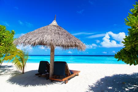 praia: Cadeiras de praia na areia da praia tropical
