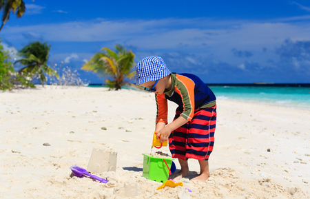 children sandcastle: little boy play with sand on beach, family vacation