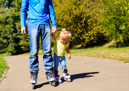 daugther: father teaching little daugther to roller skate in summer park