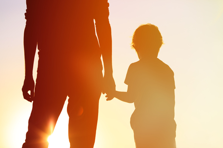 adult hand: silhouette of father and son holding hands at sunset sky