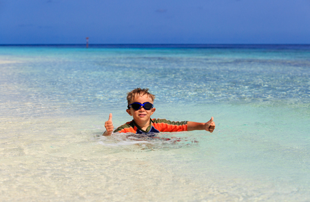 little boy swimming: happy little boy swimming at tropical beach, family vacation