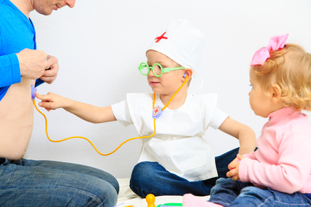 playtime: little boy and girl play doctor indoors, kids learning and playtime