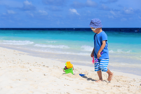 children sandcastle: little boy play with sand on beach, family beach vacation