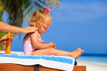 mother applying sunblock cream on daughter shoulder, sun protection Stock Photo