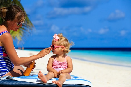 mother applying sunblock cream on daughter shoulder, sun protection 스톡 콘텐츠