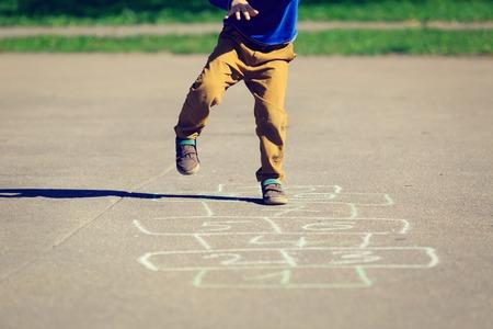 petit garçon jouant à la marelle sur aire de jeux, activités de plein air enfants