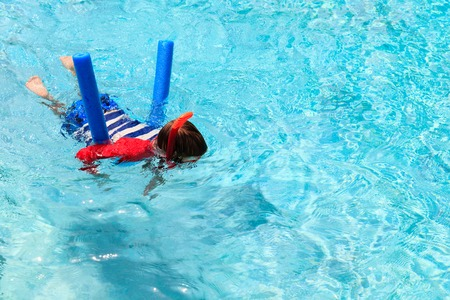learns: Little boy learns swimming alone with pool noodle and mask