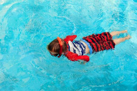 learns: Little boy learns swimming alone with mask in the pool Stock Photo