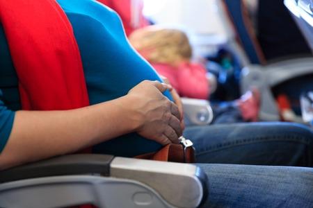 zwangere vrouw reizen met het vliegtuig, aanstaande moeder vakantie concept Stockfoto