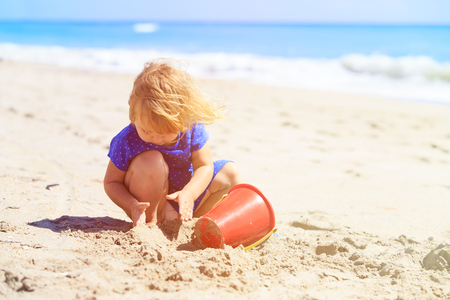 children sandcastle: little girl play with sand on beach, family vacation Stock Photo