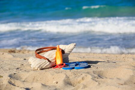 suncream: bag, suncream, flip flops on the beach, vacation concept Stock Photo