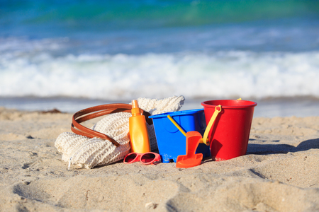 suncream: beach bag, suncream, kids toys on the beach, vacation concept