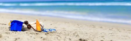 suncream: beach bag, suncream, kids toys on the beach, wide panorama