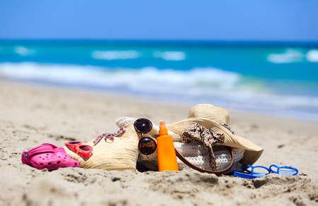 suncream: family vacation concept - beach bag, suncream, sandals on sand beach