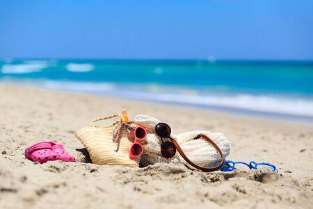 concepto de vacaciones familiares - bolsa de playa, crema solar, sandalias en la playa de arena