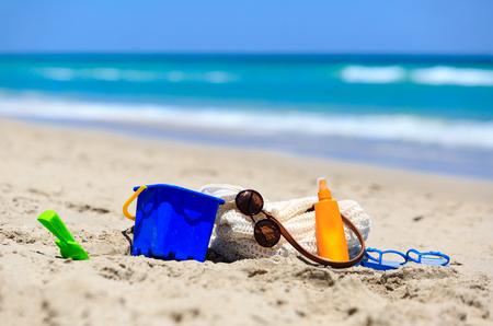 suncream: vacation concept - beach bag, suncream, kids toys on the beach Stock Photo