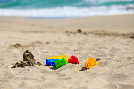 children sandcastle: kids play on sand beach concept- toys and sandcastle