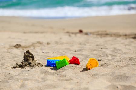 sandcastle: kids play on sand beach concept- toys and sandcastle