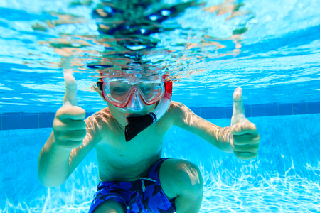cute happy little boy swimming underwater with thumbs up