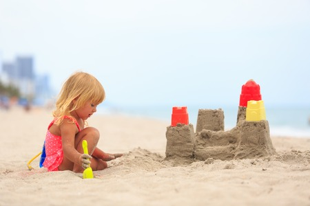 children sandcastle: cute little girl play with sand on beach