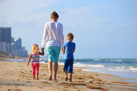 urban parenting: father and two kids walking on beach, family vacation Stock Photo