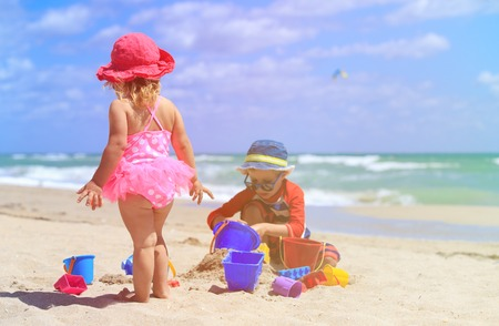 kids playing beach: little boy and girl play with sand on summer beach