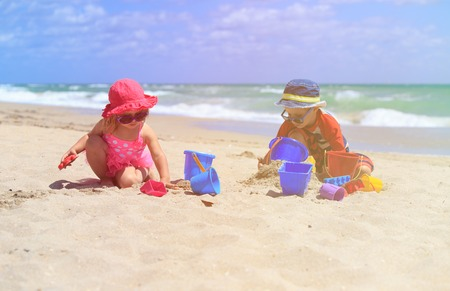 kids playing water: little boy and girl play with sand on summer beach