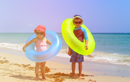 reflection of life: cute little boy and toddler girl play on sand beach