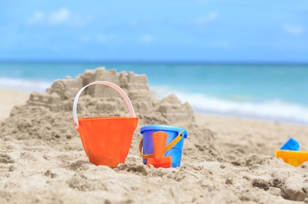 children sandcastle: kids play on beach concept- toys in sand