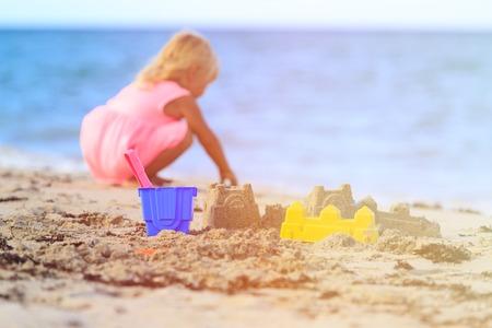 sandcastle: kids toys and little girl building sandcastle on beach Stock Photo