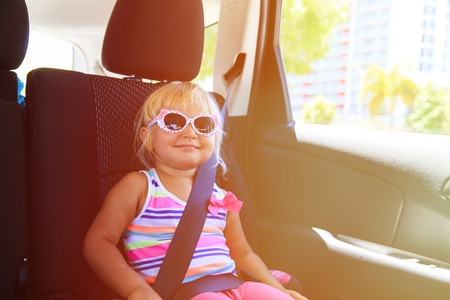 buckled: cute happy little girl enjoy travel by car Stock Photo