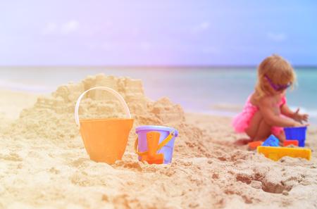 sandcastle: kids toys and little girl building sandcastle at beach