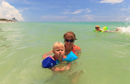 armbands: mother teaching little daughter to swim at sea, family vacation