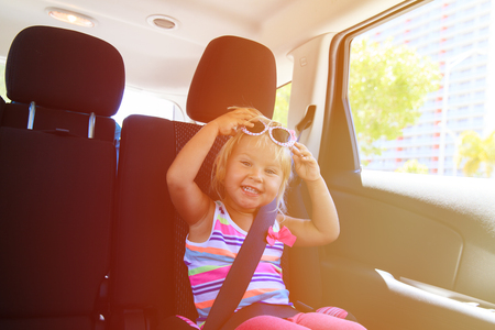 buckled: cute little girl enjoy travel by car in city