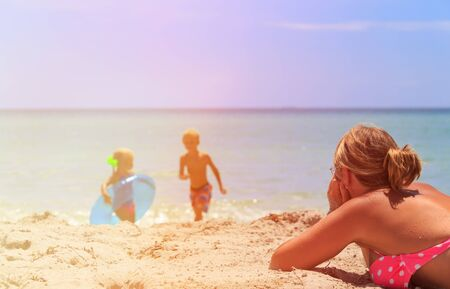 background textures: mother relax while kids play with water at beach, family vacation