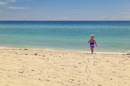 background textures: happy little girl going to swim at sand beach Stock Photo