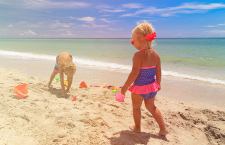 textures: little boy and girl play with sand on summer beach
